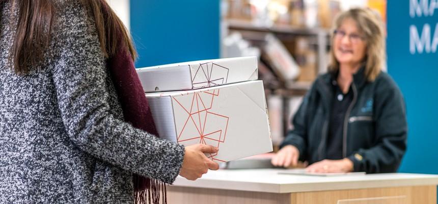 Kvinna som ger paket som ska skickas bort till personal i kassan på postkontoret i Mariehamn.